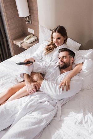 Photo pour Femme embrassant petit ami en peignoir et tenant télécommande sur le lit dans l'hôtel - image libre de droit