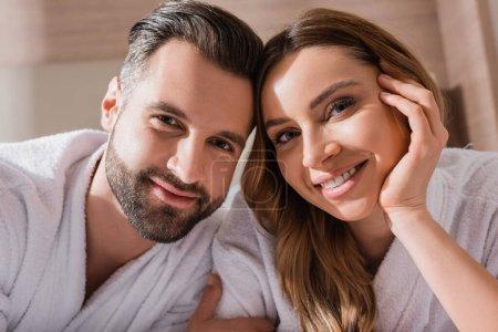 Photo pour Couple positif en peignoirs blancs regardant la caméra à l'hôtel - image libre de droit