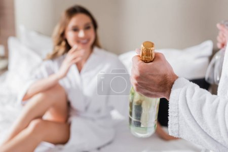 Photo for Man holding bottle of champagne near girlfriend on blurred background in hotel - Royalty Free Image
