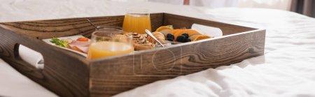 Tasty breakfast on wooden tray on white bedding in hotel, banner