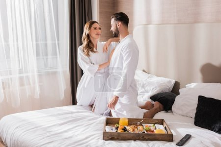 Breakfast on tray and smiling woman in bathrobe hugging boyfriend on hotel bed