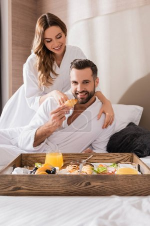 Photo for Smiling man holding croissant near girlfriend in bathrobe and breakfast on tray on blurred foreground in hotel - Royalty Free Image