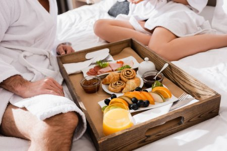 Cropped view of tasty breakfast and orange juice on tray near couple in bathrobes on hotel bed on blurred background