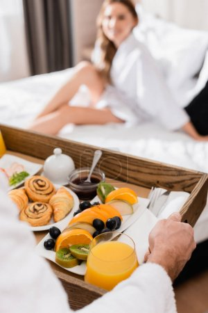 Man holding breakfast tray with orange juice and fruits near girlfriend on hotel bed on blurred background