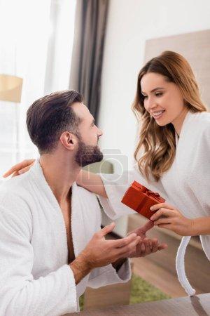 Lächelnde Frau umarmt Freund im Bademantel und hält Geschenk im Hotelzimmer