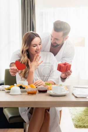 Smiling man holding present and paper heart near girlfriend in bathrobe and breakfast on blurred foreground in hotel
