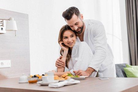 Smiling man in bathrobe hugging girlfriend near tasty breakfast in hotel room
