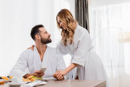 Photo pour Femme souriante en peignoir regardant petit ami avec smartphone près du petit déjeuner au premier plan flou à l'hôtel - image libre de droit