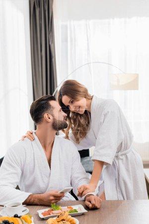 Femme souriante étreignant petit ami en peignoir avec smartphone près du petit déjeuner et café au premier plan flou dans la chambre d'hôtel