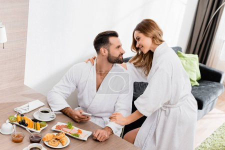 Woman in bathrobe embracing boyfriend with smartphone near delicious breakfast and coffee in hotel room