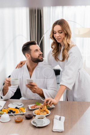 Woman taking pastry near boyfriend with cup of coffee and cellphone in hotel room
