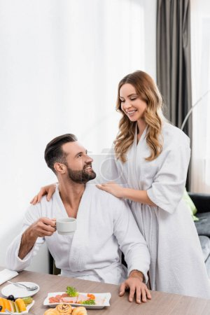 Smiling woman in white bathrobe embracing boyfriend with cup near tasty breakfast on table in hotel