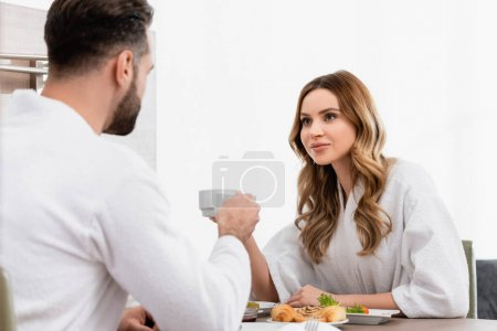 Woman in bathrobe holding cup and looking at boyfriend near breakfast on blurred foreground in hotel