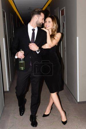 Photo pour Couple souriant en tenue formelle embrassant et tenant bouteille de champagne tout en marchant sur le couloir de l'hôtel - image libre de droit
