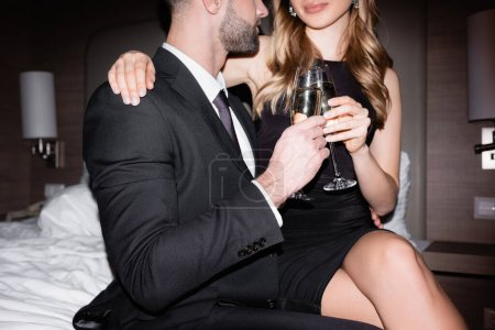 Photo pour Vue recadrée de la femme en robe tenant un verre de champagne et étreignant son petit ami en costume sur le lit de l'hôtel pendant la nuit - image libre de droit