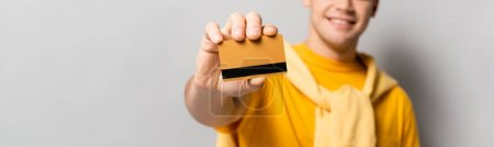 Photo for Cropped view of credit card in hand of young man blurred on grey background, banner - Royalty Free Image