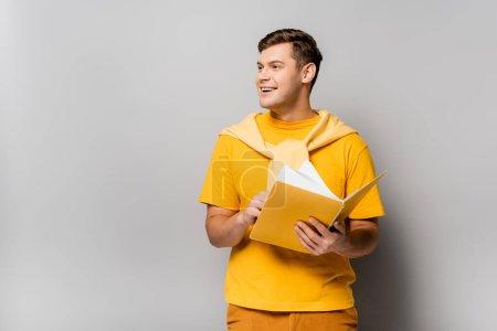 Lächelnder Student mit Notizbuch auf grauem Hintergrund