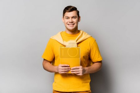 Photo for Smiling man holding yellow notebook on grey background - Royalty Free Image