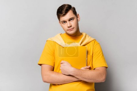 Student looking at camera while holding notebook on grey background