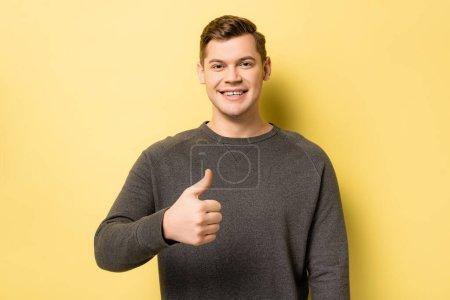 Photo pour Homme souriant montrant comme signe sur fond jaune - image libre de droit