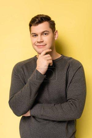 Junger Mann im grauen Pullover lächelt in die Kamera auf gelbem Hintergrund