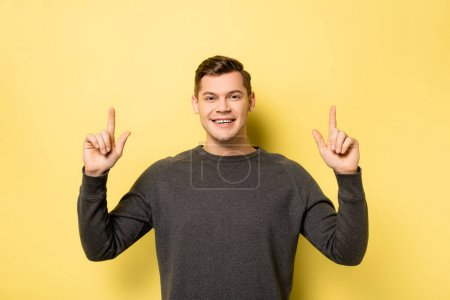 Cheerful man pointing up with fingers and looking at camera on yellow background