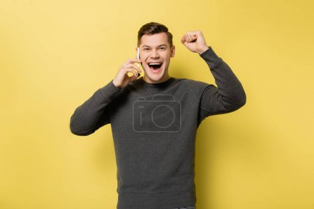 Excited man talking on smartphone and showing yes gesture on yellow background