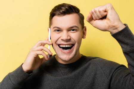 Cheerful man showing yes gesture and talking on mobile phone on yellow background