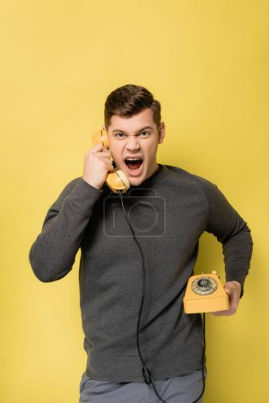 Irritated man talking on telephone on yellow background
