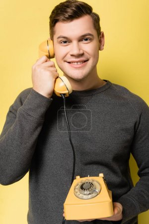 Smiling man looking at camera while talking on vintage telephone on yellow background