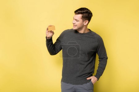 Photo for Smiling man with hand in pocket looking at credit card on yellow background - Royalty Free Image