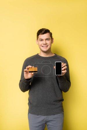 Photo pour Homme souriant montrant carte de crédit et smartphone sur fond jaune - image libre de droit