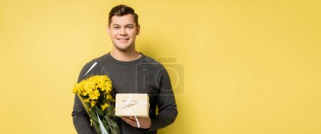 Young man smiling while holding present and flowers on yellow background, banner