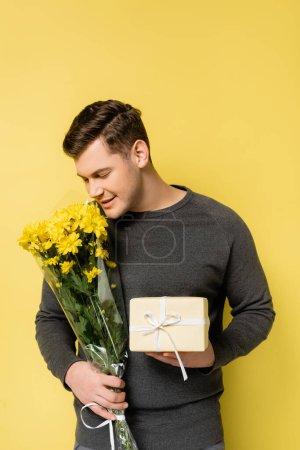 Photo pour Homme en pull gris souriant tout en tenant boîte cadeau et bouquet sur fond jaune - image libre de droit