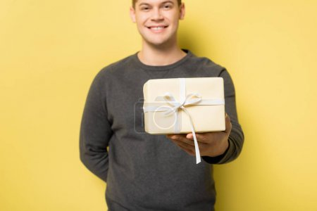 Gift box in hand of smiling man blurred on yellow background