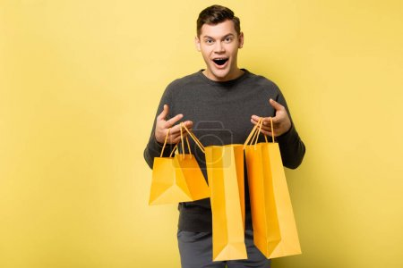 Photo for Excited man holding shopping bags on yellow background - Royalty Free Image