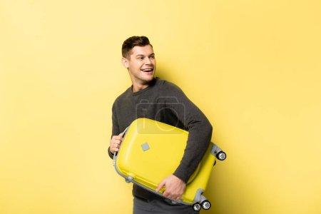 Photo pour Homme souriant tenant des bagages sur fond jaune - image libre de droit