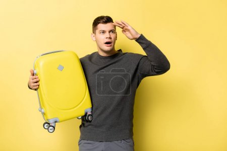 Photo for Excited man looking away while holding suitcase on yellow background - Royalty Free Image