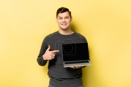 Smiling man pointing at laptop with blank screen on yellow background