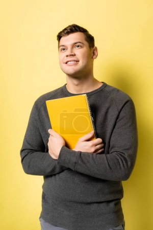 Smiling man looking up while holding notebook on yellow background