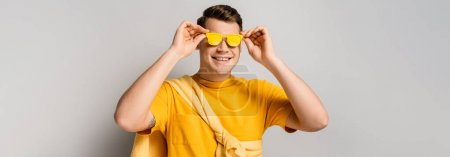 Happy man wearing yellow sunglasses on grey background, banner