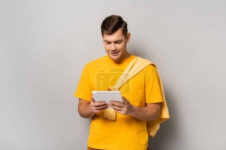 Photo pour Homme souriant en t-shirt jaune utilisant une tablette numérique sur fond gris - image libre de droit