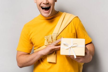 Cropped view of excited man holding present on grey background
