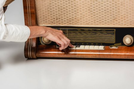 Photo pour Vue recadrée de la femme appuyant sur le bouton sur le récepteur de radio vintage sur gris - image libre de droit