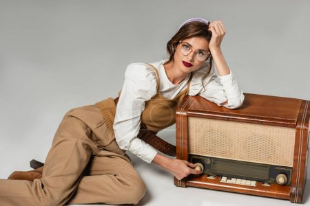 Photo for Pretty young woman looking at camera while leaning on vintage radio receiver on grey - Royalty Free Image