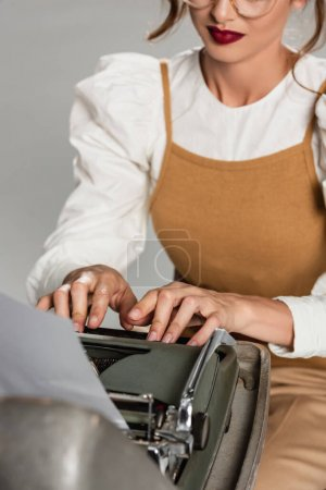 Ausgeschnittene Ansicht der Sekretärin beim Tippen auf Vintage-Schreibmaschine isoliert auf grauem, unscharfen Vordergrund