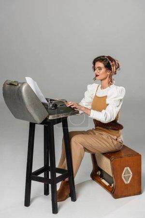 Photo pour Secrétaire en vêtements rétro assis sur récepteur de radio et tapant sur la machine à écrire vintage sur gris - image libre de droit
