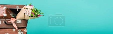 Photo pour Valises vintage et bouquet de fleurs isolé sur turquoise avec espace de copie, bannière - image libre de droit