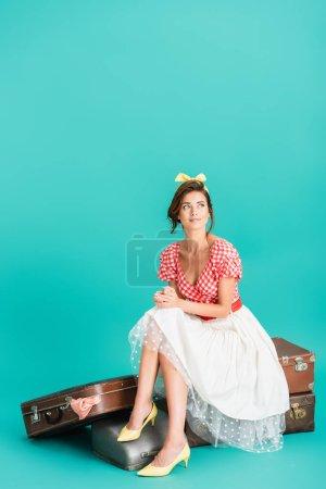 Lächelnde Pin-up-Frau schaut weg, während sie auf Vintage-Koffern auf Türkis sitzt