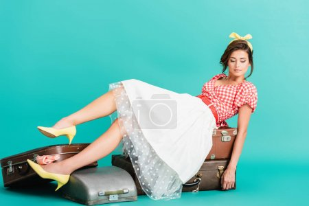 young pin up woman sitting on vintage suitcases on turquoise